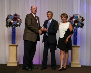 Thoroughbred trainer Phil England accompanied by his wife Debra is presented with his Hall of Fame ring by Dr. Tim Yatcak of the CHRHF Planning Committee