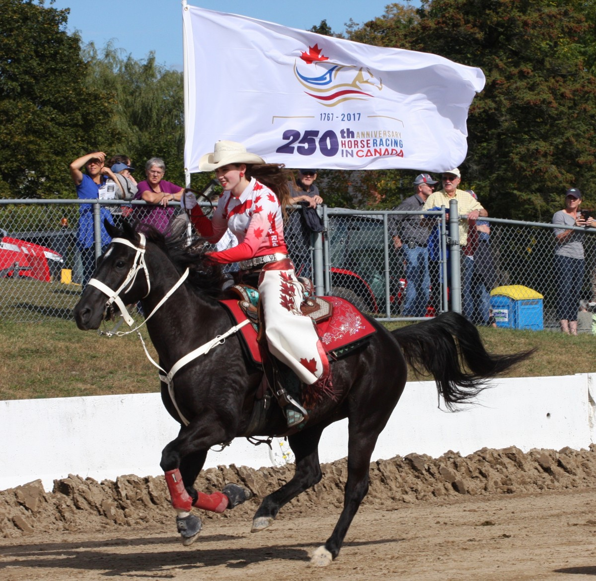 Kylie, an Erin resident who is a member of the Canadian Cowgirls sprinted with the 250th Anniversary of Horse Racing in Canada flag down a portion of the old Erin Fair Racetrack at Erin Fair Monday, Oct 9 as part of the 250 Commemorative Mile relay.