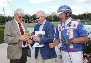August 6, 2017 — Dirk Frahm, of the German Hall of Trotting Sport receives the Hans Frömming whip from CHRHF member Bill Galvin while German harness driver Hans Wewering offers two whips signed by him as part of the reciprocal memorabilia exchange.
